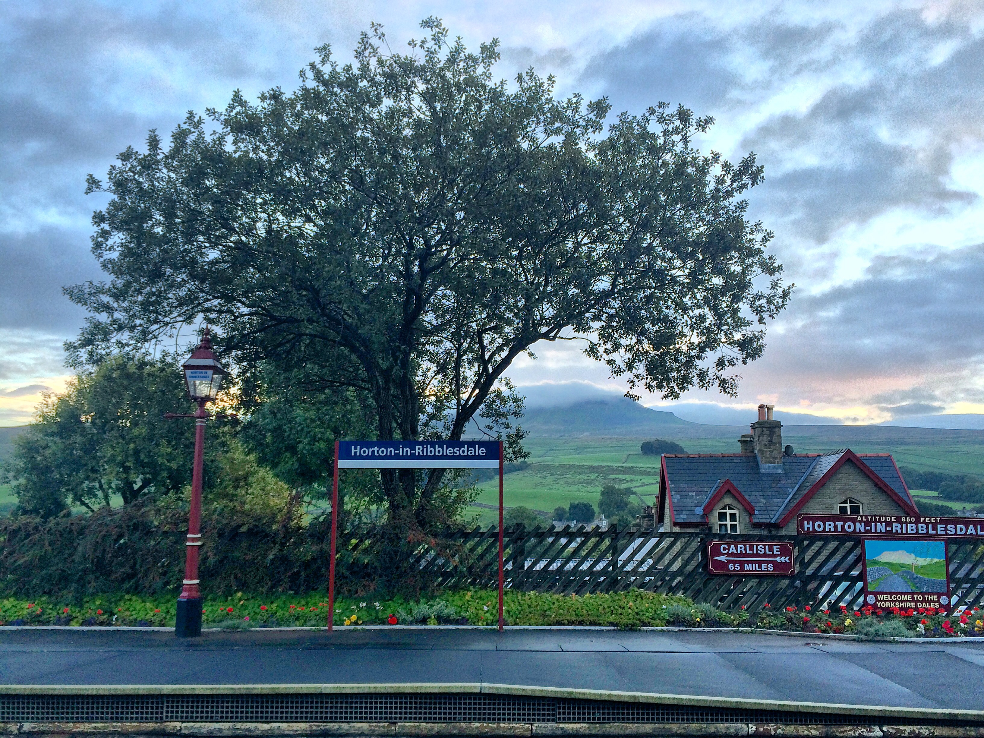 horton in ribblesdale train station with trees, fields and mountains in background