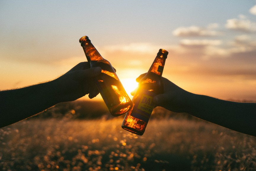 two people in a field drinking with sunset behind